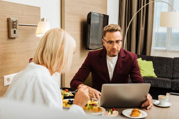 Blazer bordeaux. uomo con taglio di capelli alla moda e occhiali seduti con il laptop sul tavolo e il suo amante contro di lui