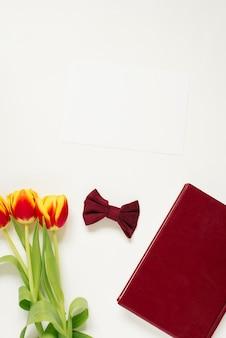 Taccuino bordeaux, fiocco, fiori su superficie bianca, vista dall'alto. spazio libero per il campo di testo, vista dall'alto. spazio libero per il testo
