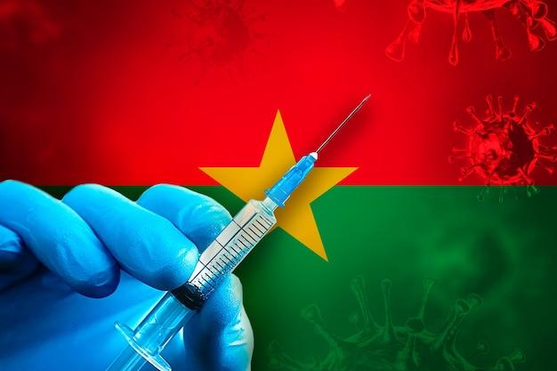 Burkina faso vaccinazione covid19 la mano in un guanto di gomma blu tiene la siringa davanti alla bandiera