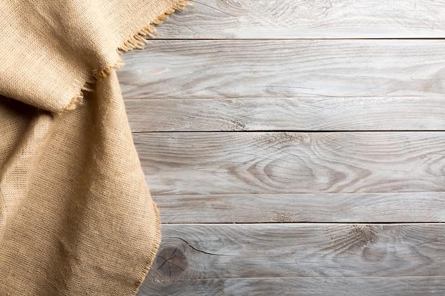 Panno di licenziamento della tela di iuta della tela da imballaggio sul fondo di legno della tavola con spazio libero.