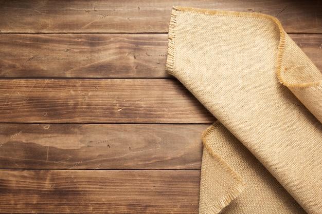 Saccheggio di tela di iuta su tavola di fondo in legno, vista dall'alto