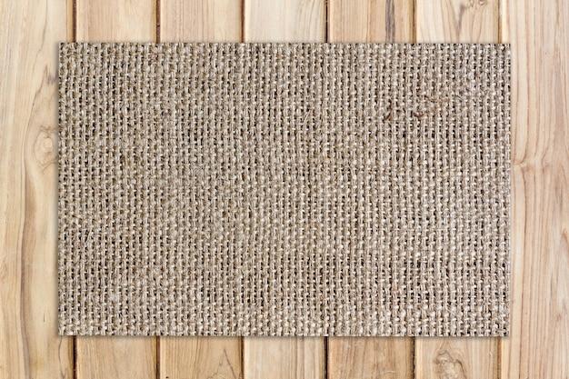 Stuoia di tela da imballaggio sulla trama di legno e priorità bassa di legno
