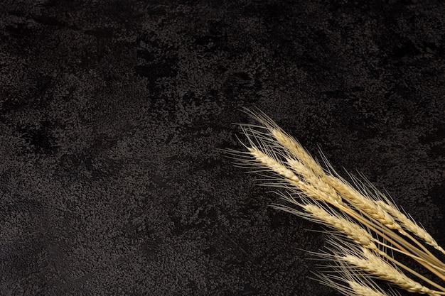 Tovagliolo di juta su uno sfondo scuro strutturale vista dall'alto spighe di grano copyspace vista dall'alto
