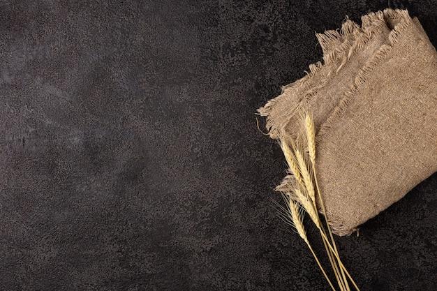 Tovagliolo di tela da imballaggio su uno sfondo strutturale scuro vista dall'alto spighe di grano copyspace