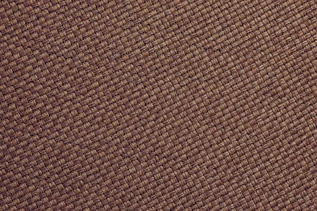 Carta da parati in tela, tessuto marrone scuro naturale, superficie in fibra. trama di tela di sacco, sfondo.