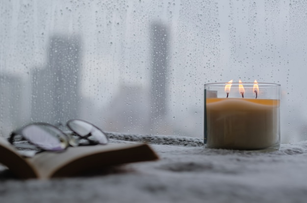 Candela aromatica accesa si mette vicino alla finestra che ha una goccia di pioggia nella stagione dei monsoni con sfondo sfocato della città. zen e concetto di relax.