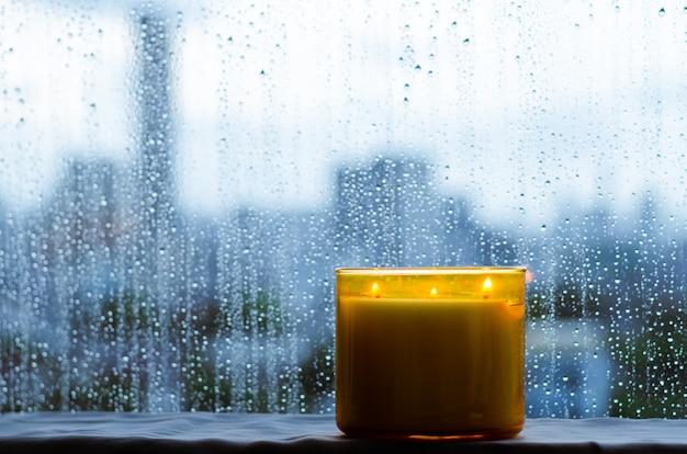 Candela aromatica che brucia si mette vicino alla finestra che ha una goccia di pioggia nella stagione dei monsoni. zen e concetto di relax.