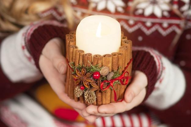 Candela accesa nelle mani di una ragazza. candela di natale. decorazioni natalizie. mani del bambino che tengono bella candela con il fuoco