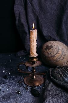 Candela e pietre che bruciano sul concetto esoterico occulto del tavolo delle streghe