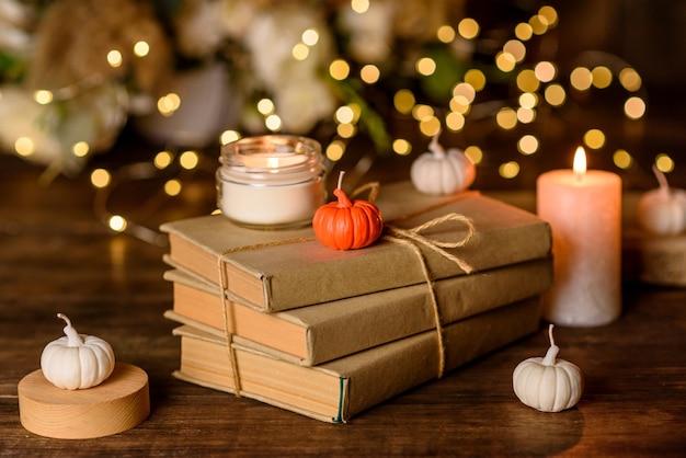 Una candela accesa su un tavolo di legno davanti a un libro a mezz'asta. apprendimento. studiare la bibbia