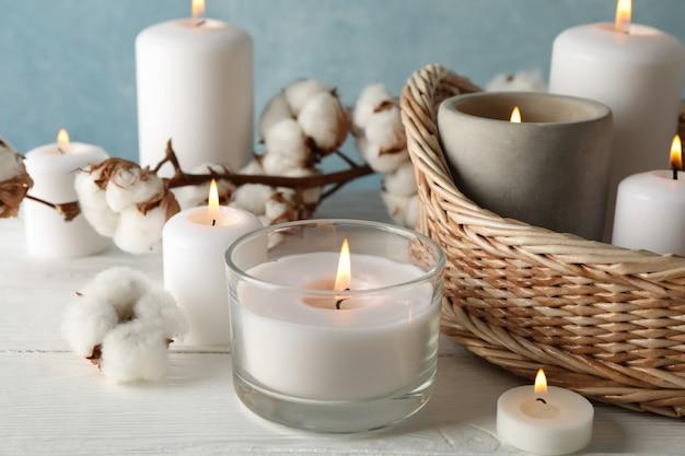 Candele, canestro e cotone brucianti sulla tavola di legno bianca