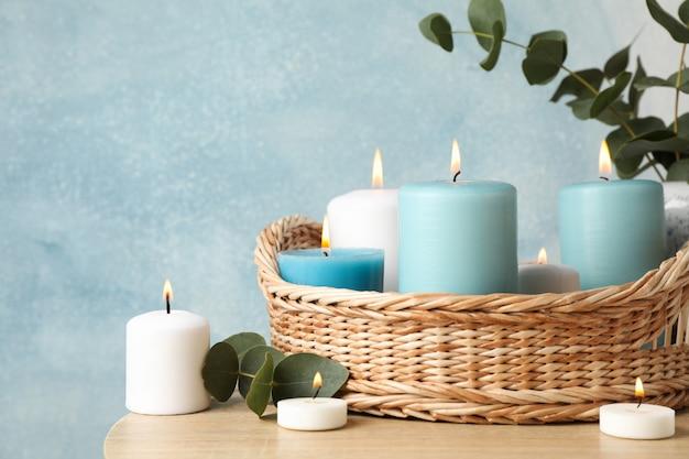 Candele, cestino e vaso brucianti con l'eucalyptus contro il blu