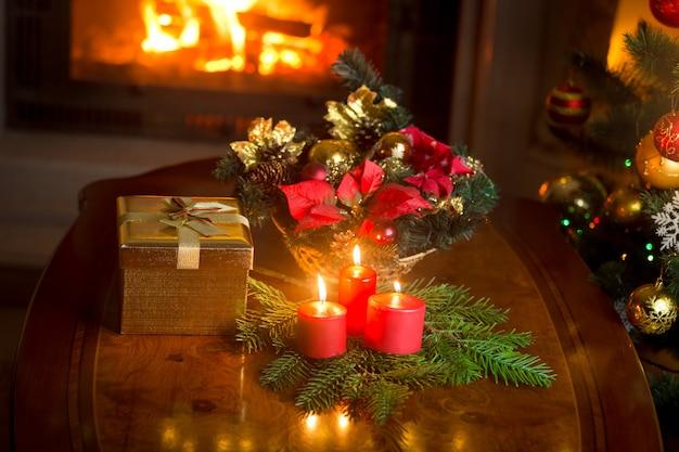 Candele accese vicino all'albero di natale decorato, confezione regalo e ghirlanda tradizionale
