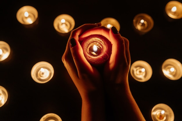 Candele accese. candela in mani femminili. molte candele accese di notte. molte candele accese.