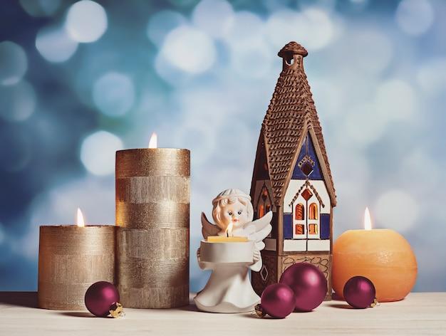 Candele accese alla vigilia di natale. un angelo è il simbolo della calda vacanza in casa.