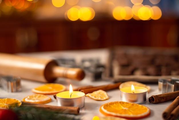 Candele accese bastoncini d'arancia essiccati di cannella vicino al mattarello e biscotti pronti al forno sul