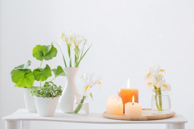 Candele accese e fiori primaverili sulla mensola in legno all'interno bianco