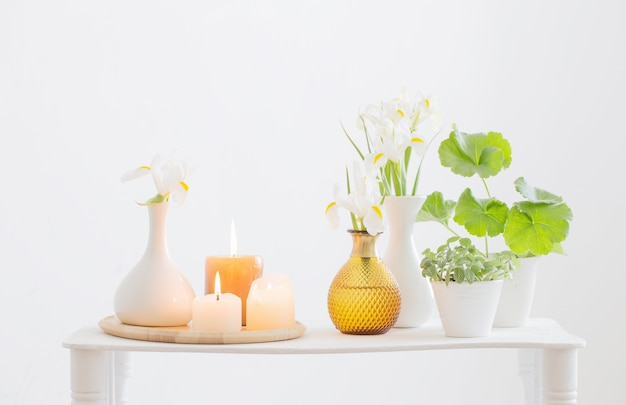 Candele accese e fiori di primavera sulla mensola in legno all'interno bianco