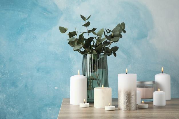 Candele e vaso brucianti con l'eucalyptus contro il blu