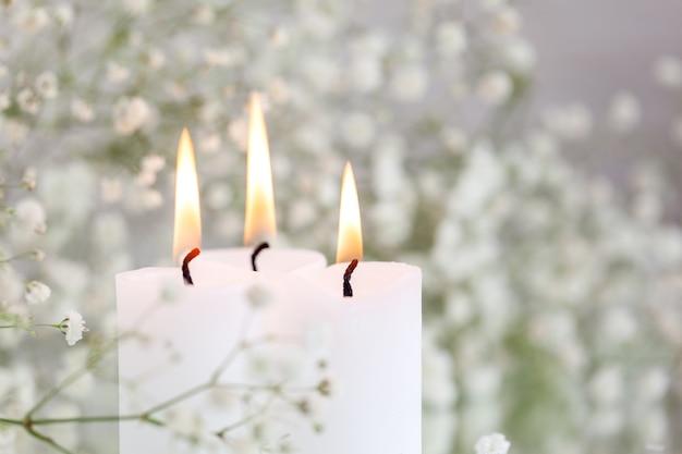 Candele accese e fiori bianchi gypsophila sul tavolo con spazio per il testo. bellissime idee di arredamento.