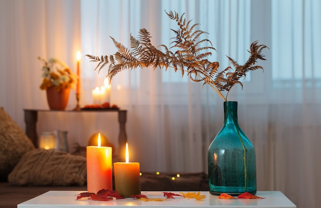 Candele accese con decorazioni autunnali sul tavolo bianco a casa
