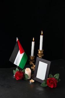 Candele accese con bandiera palestinese e fiori sulla superficie scura