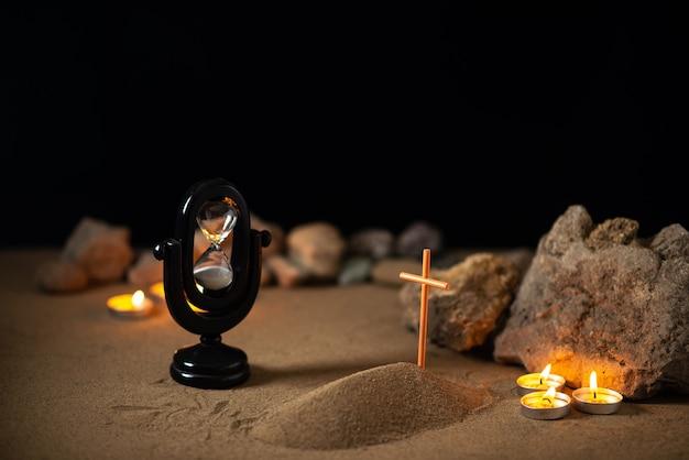 Candele accese con pietre e piccola tomba sulla sabbia come morte funebre memoria