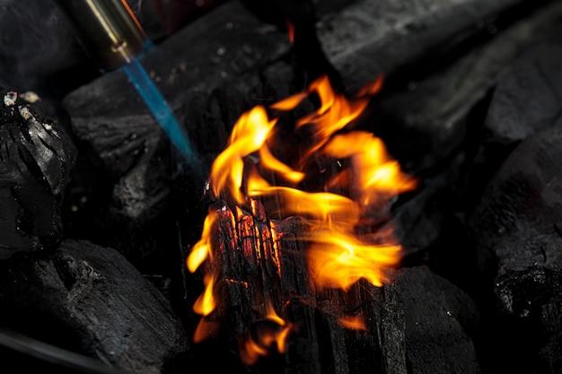 Carbone ardente da vicino. grumo di carbone sulla fiamma del gas