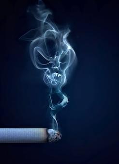 Sigaretta accesa con fumo a forma di immagine concettuale del teschio Foto Premium