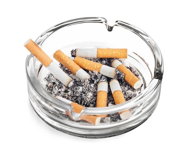Sigarette accese nel posacenere su sfondo bianco