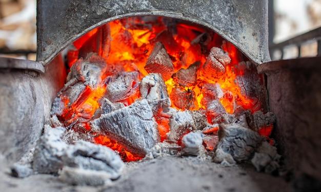 Carboni ardenti in una griglia metallica per friggere carne e verdure. cucinare su un fuoco da campo.