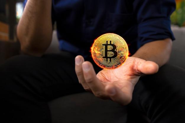 Bitcoin dorato bruciante in una mano dell'uomo d'affari nell'ufficio