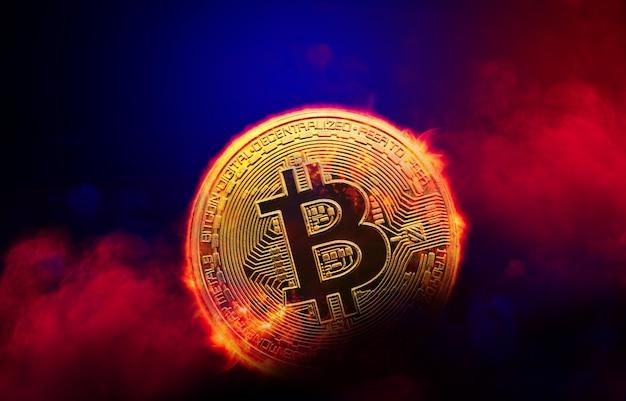 Moneta dorata bruciante del bitcoin nel fondo rosso del fumo