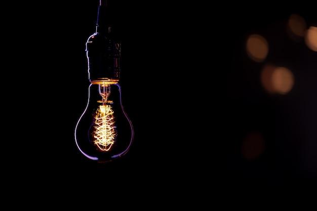 Lampada accesa appesa al buio su uno sfondo sfocato con boke.