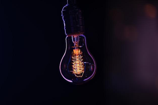 Una lampada accesa è appesa al buio su uno sfondo sfocato da vicino.