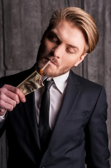 Soldi bruciati. bel giovane in abiti da cerimonia che accende una sigaretta usando cartamoneta