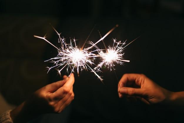 Sparkler ardente di nuovo anno. la luce del bengala si diffonde in piccole scintille.