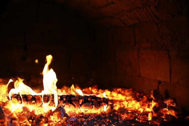 Scintille roventi brucianti volano da un grande fuoco. bellissimo sfondo astratto sul tema del fuoco. carboni ardenti, particelle in fiamme che volano via su sfondo nero.