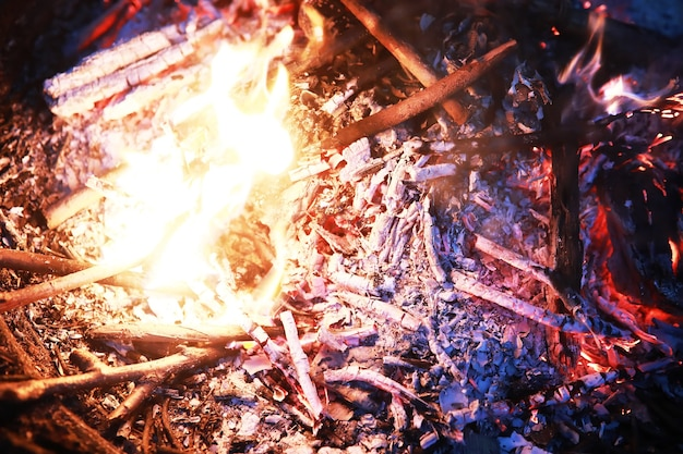 Scintille roventi brucianti volano da un grande fuoco. carboni ardenti, particelle in fiamme che volano via su sfondo nero.