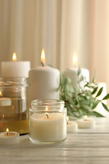 Candele profumate accese per rilassarsi sulla tavola di legno bianca