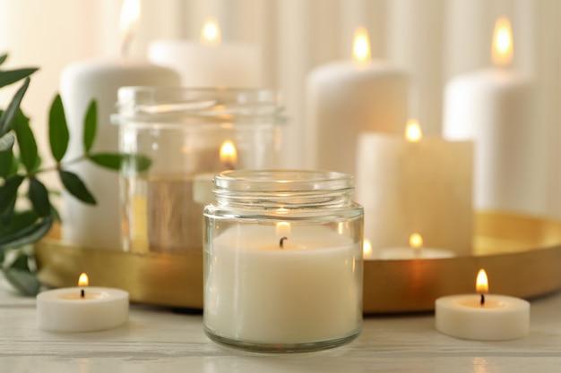 Candele profumate accese per il relax sulla tavola di legno bianco
