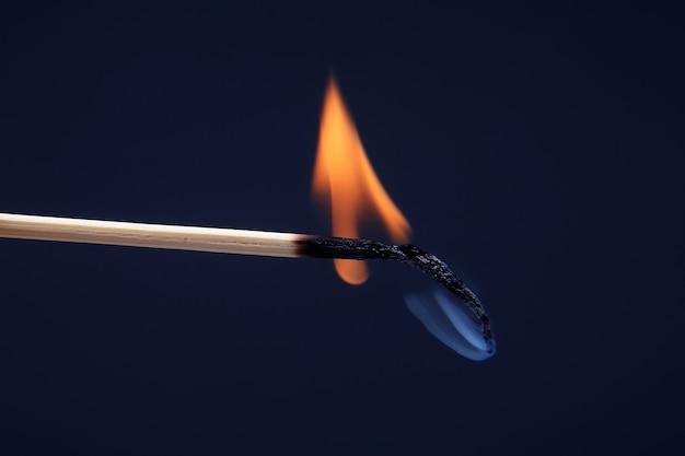 Combustione di fiammifero di legno e fumo su sfondo scuro