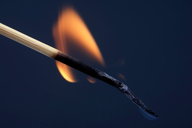 Fiammifero di legno che brucia e fuma su sfondo scuro