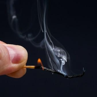 Fiammifero di legno che brucia e fuma in mano su sfondo scuro