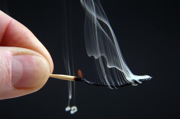 Fiammifero di legno bruciante e fumante in mano su uno spazio buio