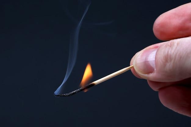 Fiammifero di legno bruciante e fumante in mano su oscurità