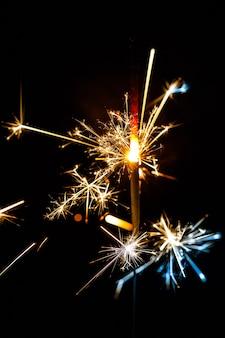 Sparkler burning isolato su sfocatura dello sfondo nero