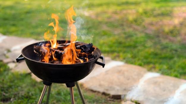 Bruciare legna nella griglia del barbecue, preparare carboni ardenti per grigliare carne nel cortile sul retro.
