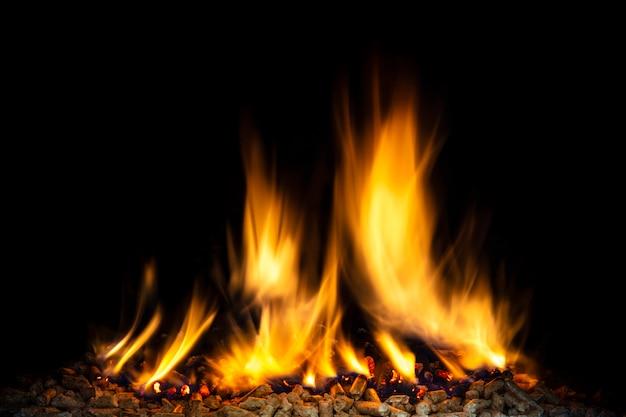 Pellet di legno che brucia, fiamma visibile e sfondo scuro.