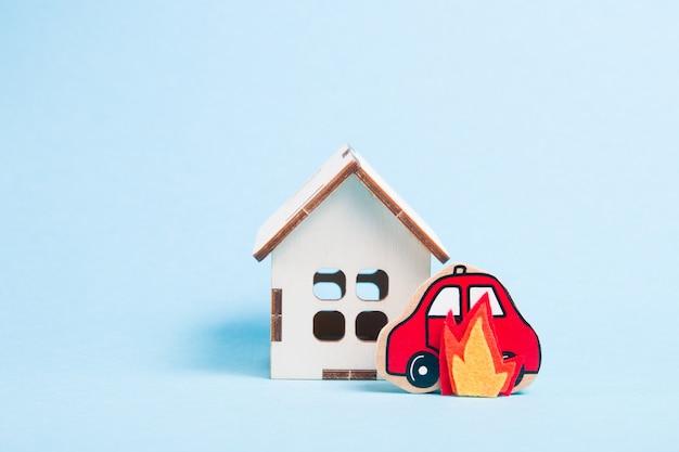 Modello di auto in legno e casa in fiamme